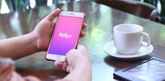 Pessoa com celular com aplicativo Meliuz aberto