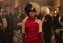 Cruella, personagem do filme de mesmo nome, em cena, com vestido vermelho.