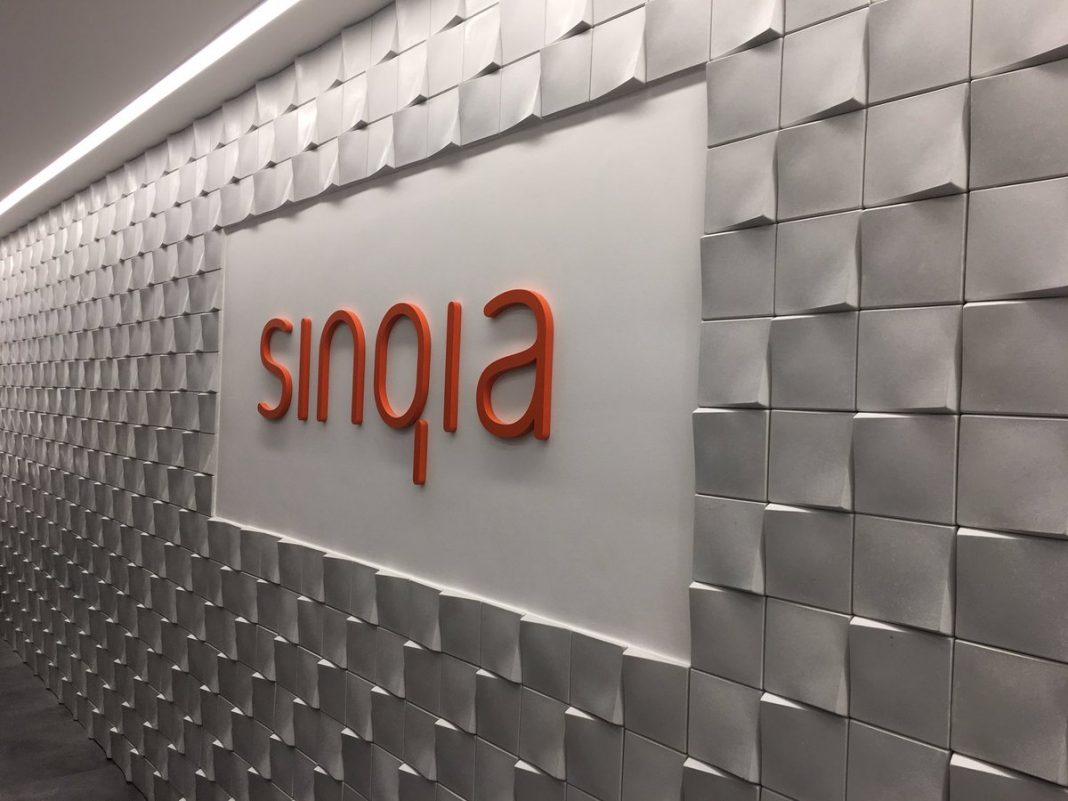 Foto de parede com o logo da Sinqia em laranja no meio